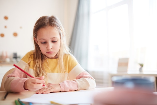 Warm toned portrait of cute little girl drawing pictures or doing homework while sitting at table in home interior, copy space