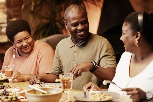 Warm toned portrait of happy africanamerican family enjoying dinner together outdoors at evening