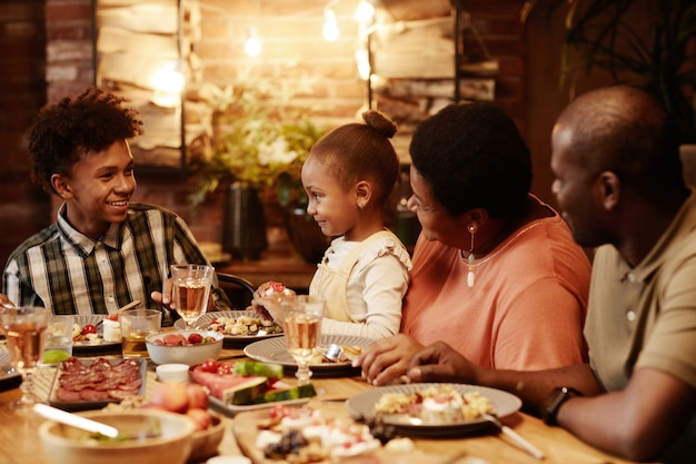 Warm toned portrait of happy africanamerican family enjoying dinner together outdoors with focus on ...