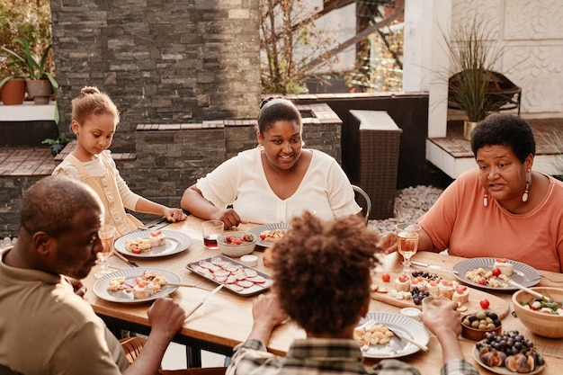 Warm toned portrait of happy africanamerican family sitting at table outdoors and enjoying dinner to...