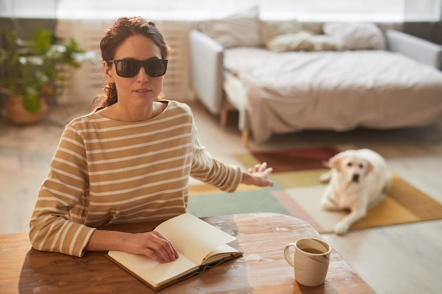 Warm toned portrait of modern blind woman reading braille book while sitting at table in cozy home interior and reaching for guide dog, copy space