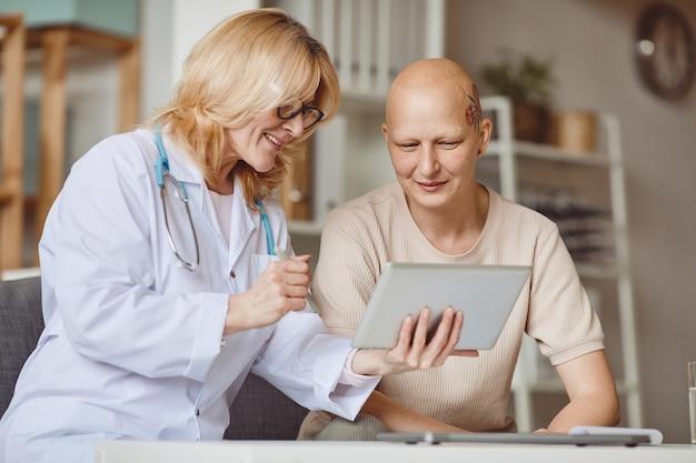 탈모 및 암 회복에 대한 여성 의사와 상담하는 동안 디지털 태블릿을보고 대머리 여자의 따뜻한 톤의 초상화