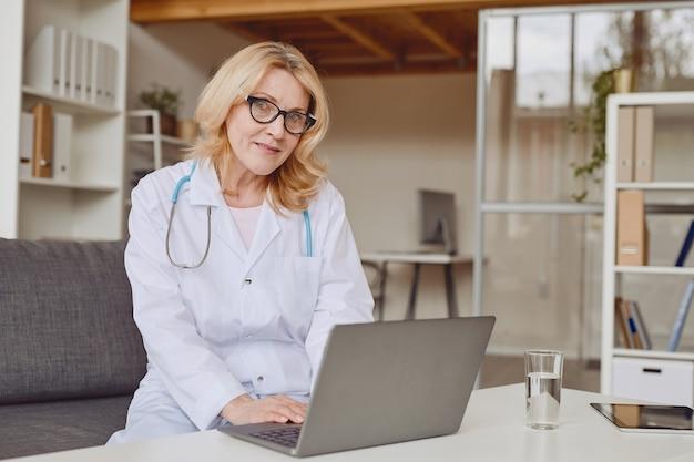 노트북을 사용하고 현대 병원에서 작업하는 동안 카메라에 웃고 쾌활한 여성 의사의 따뜻한 톤 초상화, 복사 공간