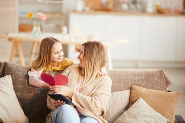 母の日またはバレンタインデーに母親にカードを与えるかわいい女の子の暖かいトーンの肖像画、コピースペース