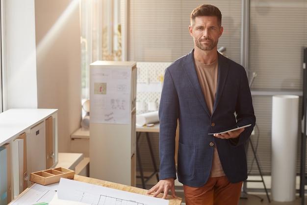 사무실에서 책상에 서있는 동안 잘 생긴 성숙한 남자의 따뜻한 톤의 초상화,