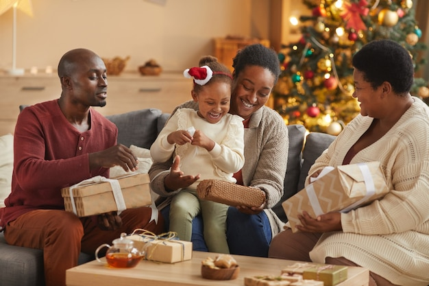 Портрет в теплых тонах счастливой афро-американской семьи, открывающей рождественские подарки, наслаждаясь праздничным сезоном дома