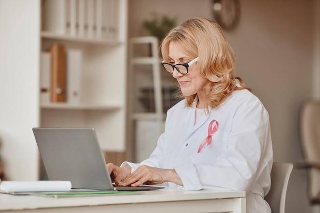 현대 사무실, 유방암 인식 기호, 복사 공간에서 노트북에서 작업하는 동안 핑크 리본이 달린 성숙한 여성 의사의 따뜻한 톤의 초상화는 흰색 실험실 코트에 고정