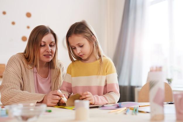 Портрет в теплых тонах зрелой матери, увлекающейся искусством и рукоделием с милой дочерью в домашнем интерьере, копия пространства