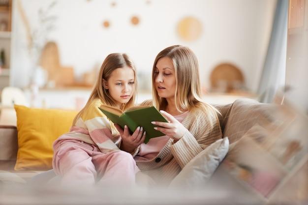 Теплый тон портрет зрелой матери, читающей книгу маленькой девочке, сидя на диване в уютном домашнем интерьере, копия пространства