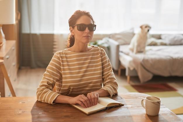 盲導犬を背景に、居心地の良い家のインテリアのテーブルに座って点字の本を読んでいる現代の盲目の女性の暖かいトーンの肖像画、コピースペース