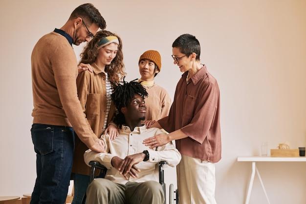 지원 그룹, 복사 공간에서 치료 세션 동안 휠체어에 젊은 남자를 위로하는 사람들의 따뜻한 톤의 초상화