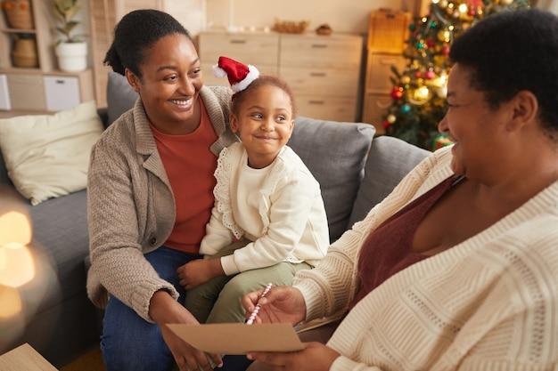 Портрет улыбающейся афроамериканской семьи в теплых тонах, которая пишет письмо санте с милой маленькой девочкой, наслаждаясь рождественским сезоном дома