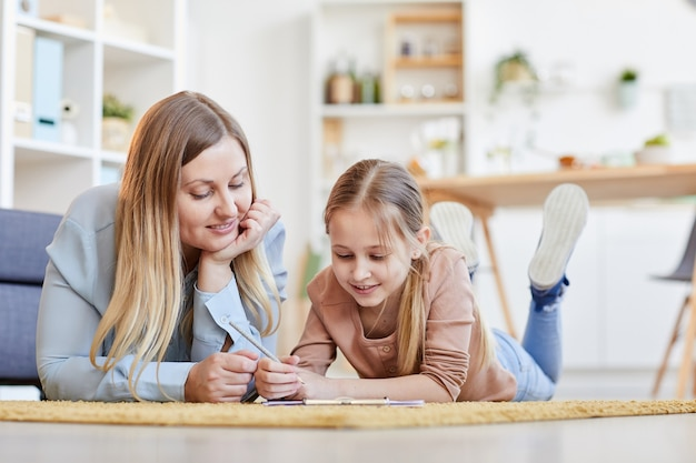 Портрет улыбающихся матери и дочери в теплых тонах, лежащих на ковре вместе во время рисования или учебы в уютном домашнем интерьере, копия пространства