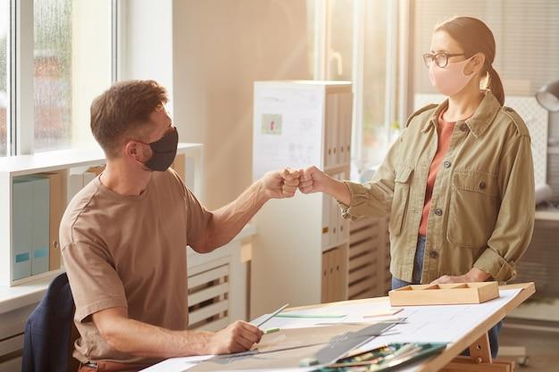 パンデミック後のオフィスで非接触型の挨拶として拳をぶつけるマスクを身に着けている2人の同僚の温かみのあるトーンの肖像画