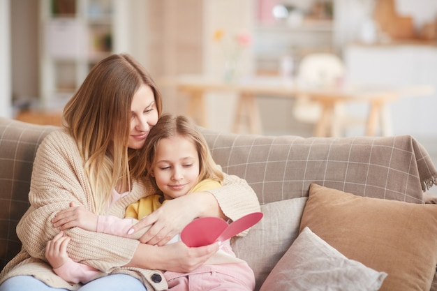 Warm-toned portrait of smiling mother embracing daughter while reading handmade card on mothers day, copy space