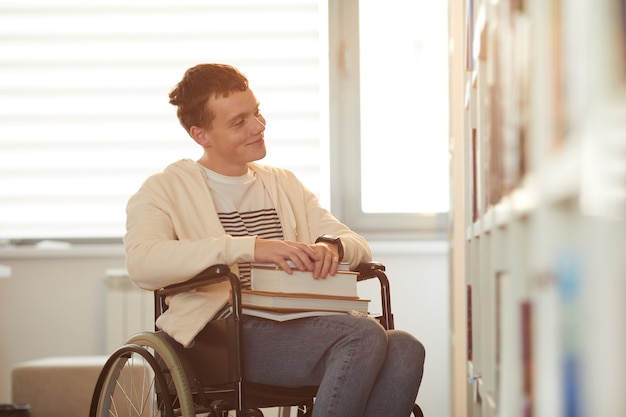 Warm toned portrait of young man using wheelchair in school while looking at bookshelves in library lit by sunlight