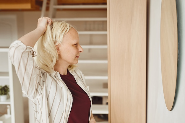 Warm-toned side view portrait of bald woman taking off wig while standing by mirror in home interior, alopecia and cancer awareness, copy space