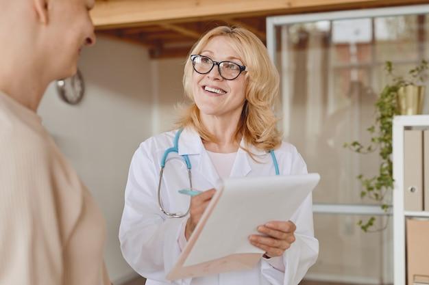 탈모 및 암 회복에 대한 상담 중에 대머리 환자와 이야기하는 쾌활한 여성 의사의 따뜻한 톤의 허리 위로 초상화, 복사 공간