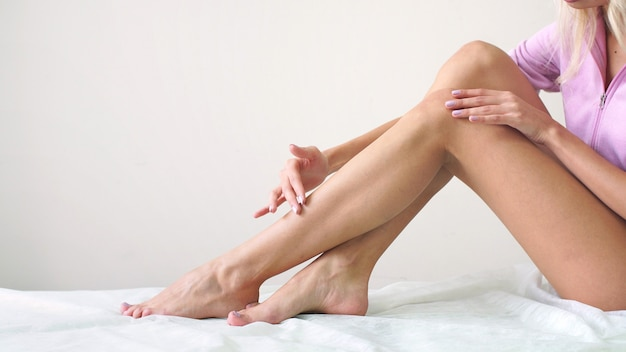 Warm wax on women's feet, professional depilation hair removal in the studio