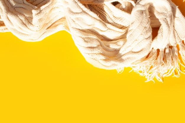 Теплый белый вязаный шарф на желтом фоне. вид сверху