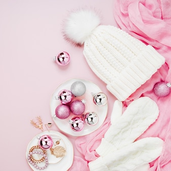 暖かい冬の服とクリスマスの装飾。パステルピンクカラーのアレンジ。