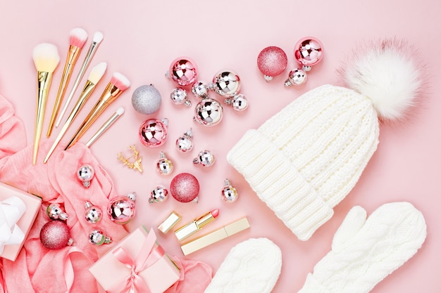 暖かい冬の服、化粧品、クリスマスの装飾。パステルピンクカラーのアレンジ。