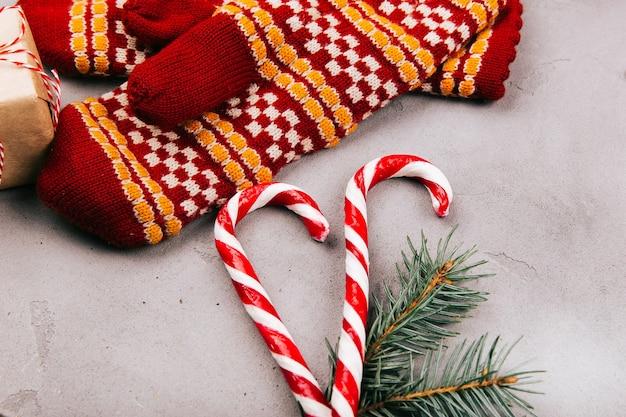 Теплые зимние перчатки, красные белые конфеты и пихта на сером полу