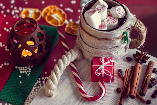 Warm winter mug with marshmallow, striped lollipop and gift