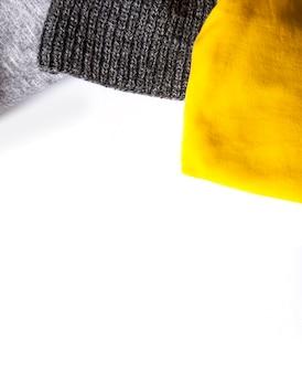 白い背景の上の暖かい冬の服。スペースをコピーします。黄色とグレーの流行のファッションカラー。ニットのジャンパーとチェック柄。