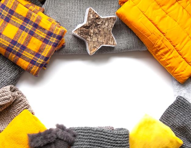 白い背景の上の暖かい冬の服。スペースをコピーします。黄色とグレーの流行のファッションカラー。ニットのジャンパー、ジャケット、ミトン、チェック柄。