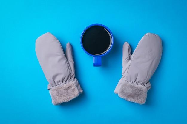 Теплые женские варежки и чашка кофе на синей поверхности. горячий напиток и варежки.