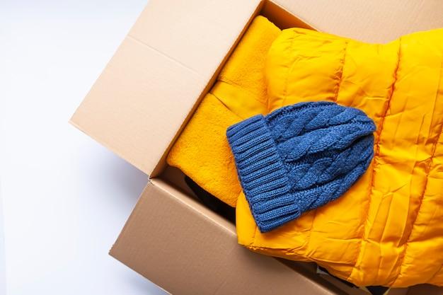 開いた段ボール箱に暖かい黄色のジャケットと青いニット帽。ファッション衣装。明るい色。ホームストレージ。
