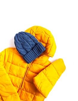 白地に暖かい黄色のジャケットと青いニット帽。ファッション衣装。明るい色。ホームストレージ。小さなスペースの整理。
