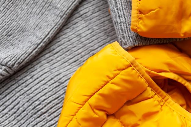暖かい黄色のジャケットとウールのニットジャンパー。ファッション衣装。明るい流行色。ホームストレージ。小さなスペースの整理