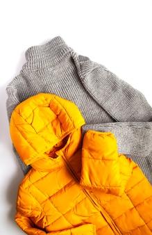 暖かい黄色のジャケットと白い背景のウールのニットジャンパー。ファッション衣装。明るい流行色。ホームストレージ。小さなスペースの整理。