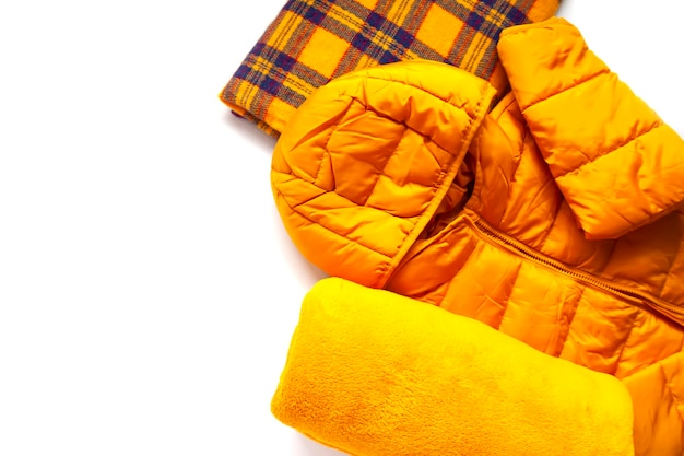 暖かい黄色のジャケットと白い背景のウールの柔らかい格子縞。ファッション衣装。明るい色。ホームストレージ。小さなスペースの整理。