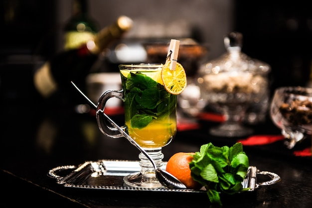 Согревающий алкогольный коктейль с мятой, медом, сиропом, банкой мандарина на прилавке, на темном столе. сангрия, пунш