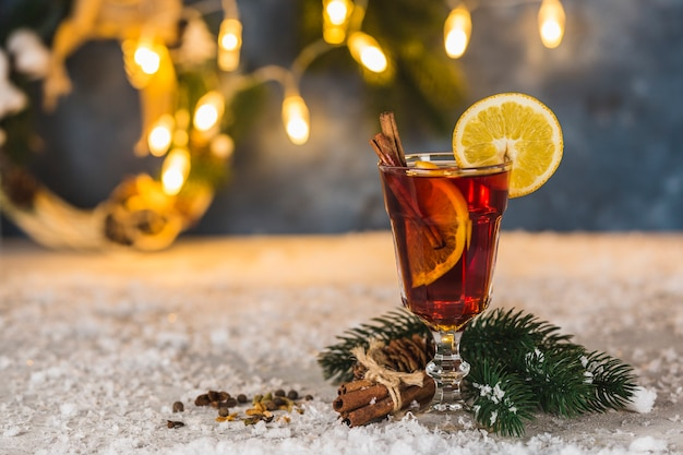 Warming alcoholic drink mulled wine with cinnamon and orange slices on the background with spruce branches a
