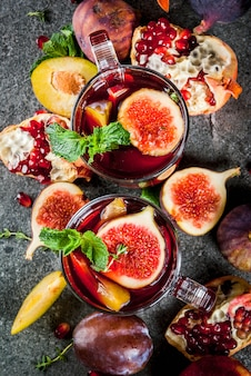 Warming autumn, winter cocktail drinks recipes. hot red fruit sangria with apples, plums, figs, pomegranate, mint, cinnamon, thyme, lemon. on dark stone table top view