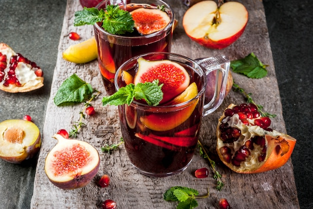 Warming autumn, winter cocktail drinks recipes. hot red fruit sangria with apples, plums, figs, pomegranate, mint, cinnamon, thyme, lemon. on dark stone table, with wooden cutting board,