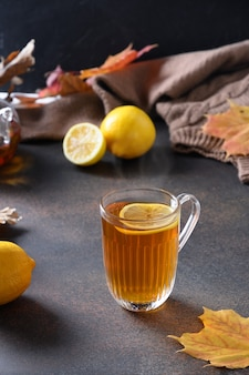 Warming black tea with lemon in cozy lifestyle with fall leaves and cozy scarf on brown space