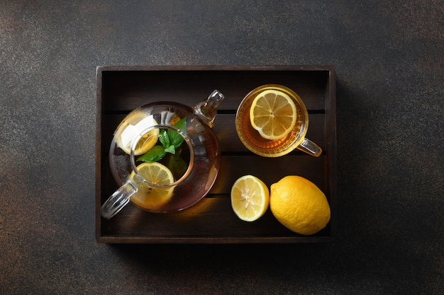 Warming black tea with lemon in cup and glass teapot on brown space