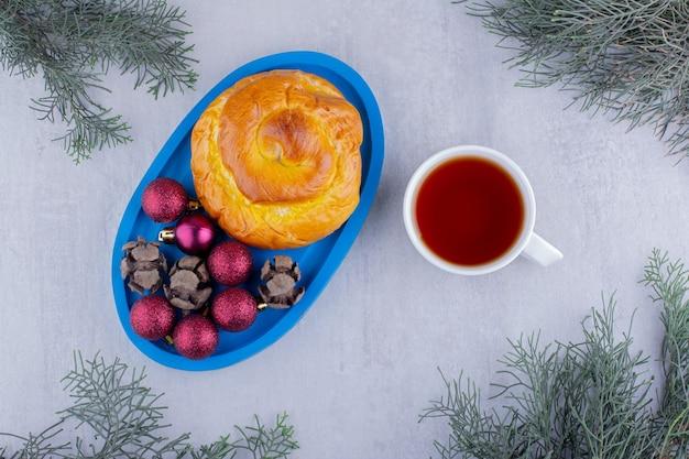 Согревающая чашка чая рядом с тарелкой сладкой булочки и рождественских украшений на белом фоне.