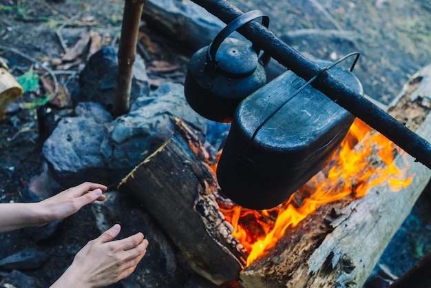 Warming hands by fire at camping. cauldron and kettle above bonfire. cooking of food on nature. dinner outdoors. firewood and branches in fire. active rest in forest.