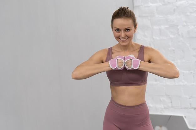 Прогревание оружия в защитных тренировочных перчатках молодая женщина тренируется