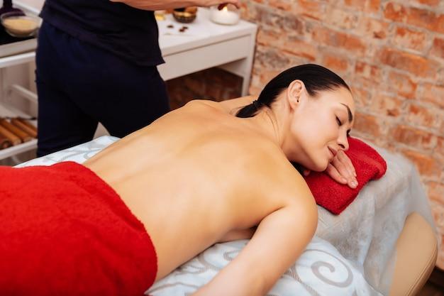 背中をウォーミングアップ。赤いタオルで覆われたお腹の上に横たわる愉快な黒髪の女性が、瞑想的な時間を過ごす準備をしている