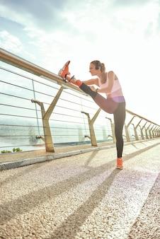 Разминка перед бегом, вид сбоку позитивной женщины-инвалида в спортивной одежде и растяжке в наушниках