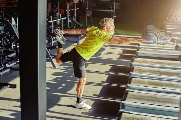 워밍업은 스트레칭을 하는 운동복을 입은 성숙한 운동 남자의 전체 길이 샷을 연습합니다.