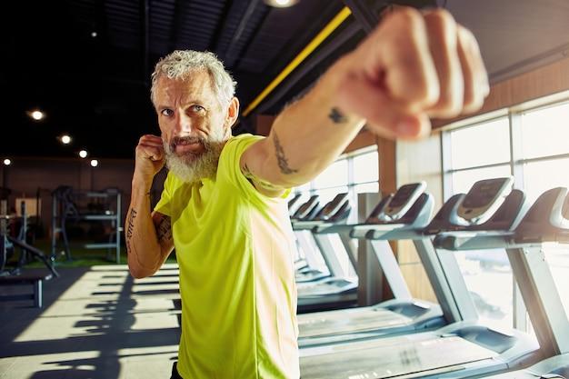 男性の顔に焦点を当てたジムでワークアウトしながらスポーツウェアボクシングで集中した成熟した男性をウォーミングアップ
