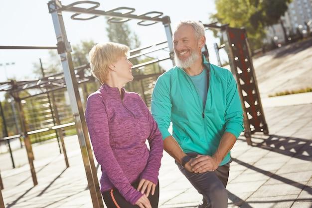 경기장 남자에서 함께 체조를 하는 운동복을 입고 행복한 성숙한 가족 커플을 워밍업